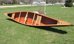 This Cedar strip canoe features caned seats and two carry handles in Birds Eye Maple, Ash carrying yoke, 3/8? brass stem bands and copper style deck rings. It has an epoxy graphite base at the 3? waterline. Also comes with 2 shaft bent paddles. Weighs 57
